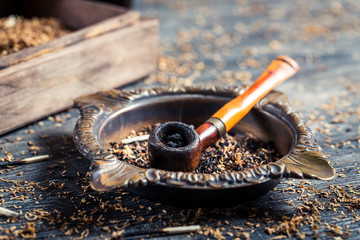 Closeup of old wooden pipe in ashtray