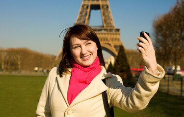 Happy beautiful woman in Paris using phone camera