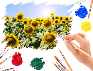 Hand with a brush painting summer landscape with sunflowers