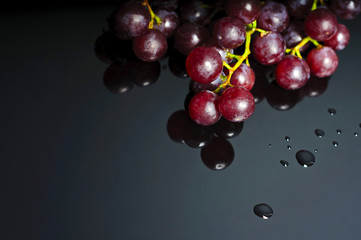 Grapes on dark reflective background, macro with blank space