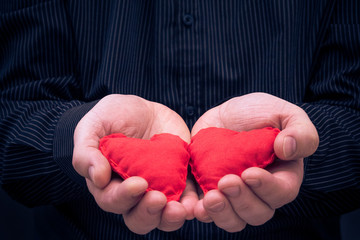 two red hearts held male hands