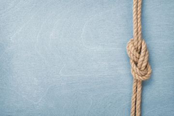 Ship rope knot on wooden texture background