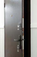 Opened metal door with keys in keyhole