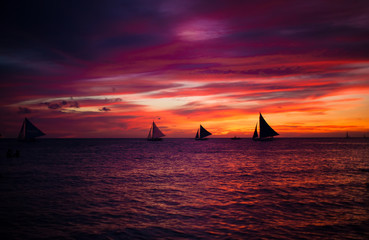 Incredible beautiful sunset with sailboat on the horizon in