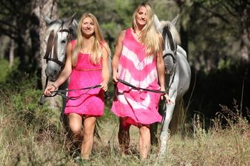 Mädchen mit rosa Kleidern und Pferden