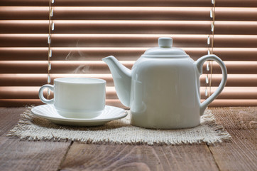 tea cup with teapot on old wooden table