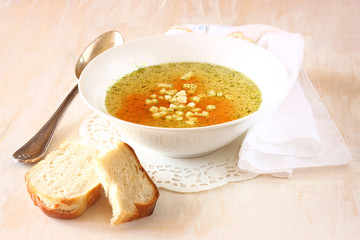 chicken soup with carrots over white wooden textured background