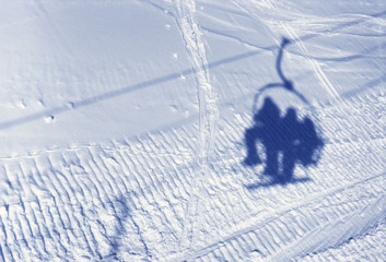 Shadow of ski lift and people on snow