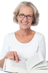 Smiling senior woman reading a book