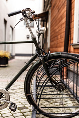 In de dag Fiets Fragment of a bike parked near a wooden house