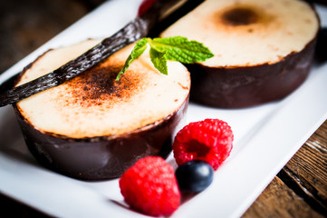 Creme brulee with vanilla sticks and berries on wooden backgroun