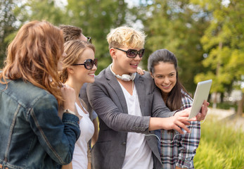 teenagers taking photo with tablet pc outside