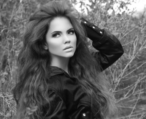 Outdoors portrait of beautiful brunette woman with long wavy hai