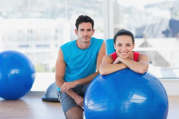 Instructor and smiling woman with exercise ball at gym