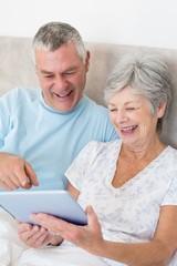 Senior couple using digital tablet in bed