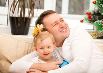 Happy father and child girl hugging and laughing at home.
