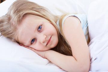 Kid girl lie on bed.