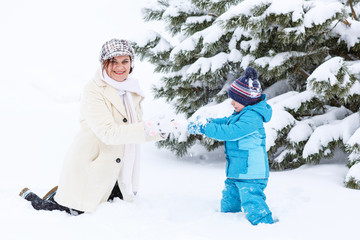 Little preschool boy and his mother playing with first snow in p