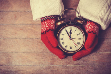 Hands in mittens holding gretro clock