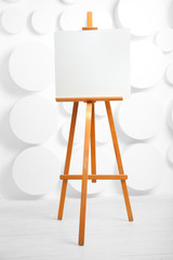 wooden easel with blank canvas in the studio