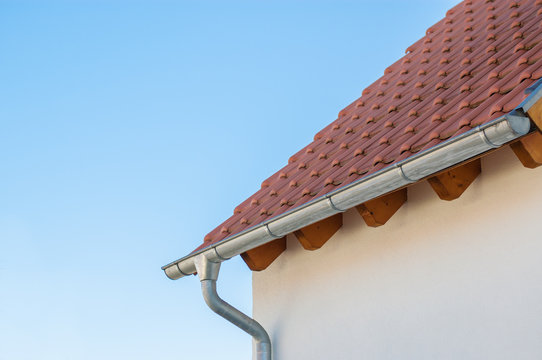 Corner of the house with tile roof on a background of blue sky