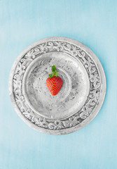 Half strawberry on silver platter , blue background, top view