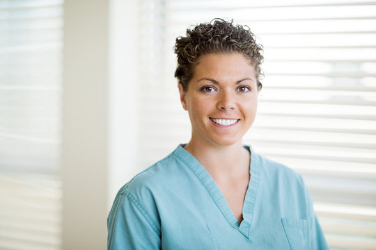 Happy Female Nurse In Scrubs