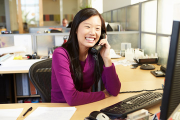 Fototapete - Asian Woman On Phone In Busy Modern Office