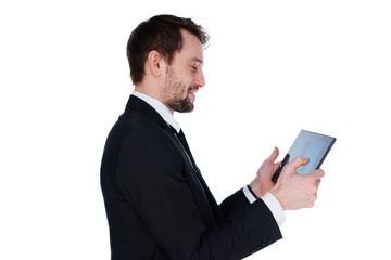 Smiling businessman looking at his tablet-pc