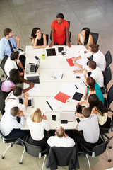 Fototapete - Businesswoman Addressing Meeting Around Boardroom Table