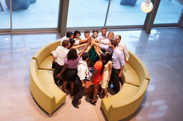 Fototapete - Businesspeople Giving Each Other High Five In Office Lobby