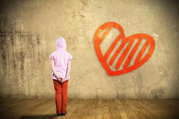 kleines Kind vor einer Wand mit aufgemaltem Herz