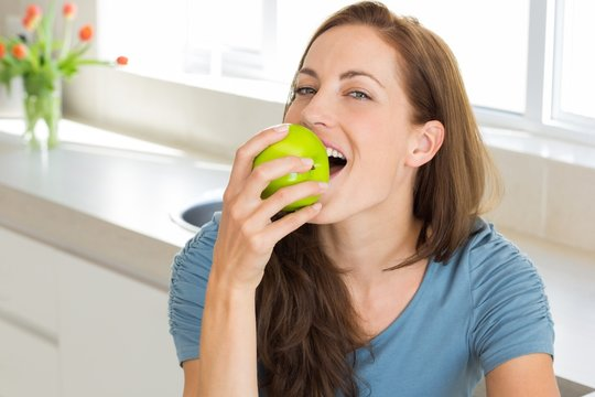 Smiling young woman eating apple in kitchen