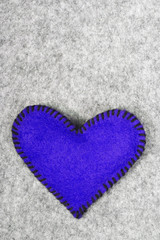 navy blue felt heart on a gray background