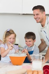 Children with father baking cookies at counter top