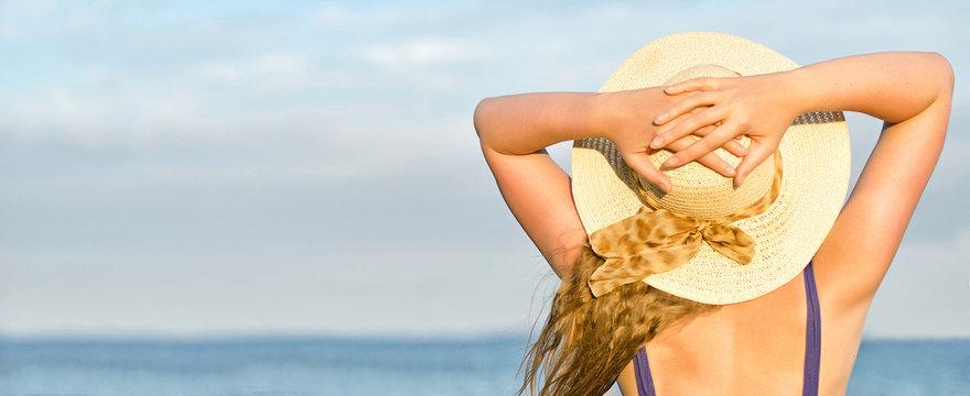 Woman in straw hat sunbathing near the sea.
