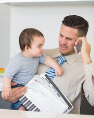 Businessman carrying baby and documents while on call