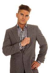 man hold gray jacket very serious