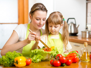 mother teaching kid daughter mixing salad at kitchen