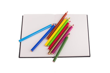 Color pencils placed on notebook, isolated on white