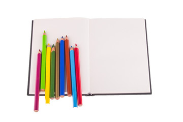 Color pencils placed on notebook, isolated on white background.