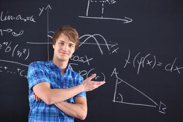 Młody zadowolony uczeń przy tablicy