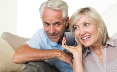 Mature couple using a smartphone on sofa