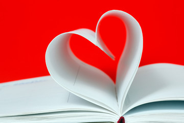Heart shape of diary pages on a red background