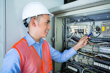 Asian Electrician at panel on construction site