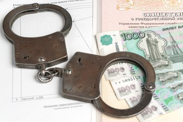 Handcuffs and money against the background of the certificate of