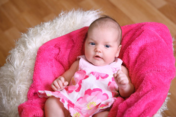 baby girl in the dress on a pink plaid