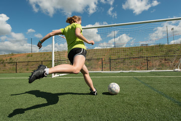 Female soccer player shooting on goal wide low angle