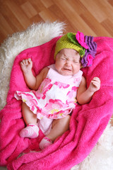 crying baby girl in the dress on a pink plaid