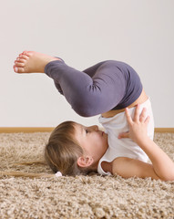 Cute little girl yoga exercising